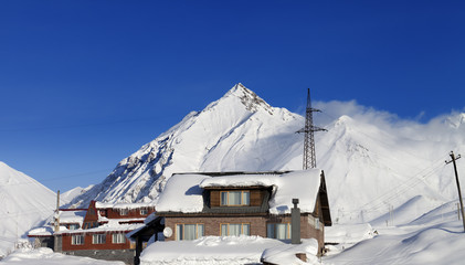 Hotels in winter snowy mountains at sun day