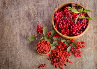 Barberry and dry goji berries in two bowls on wooden background