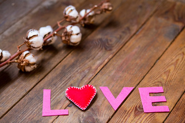 red heart and gossypium on the wooden background