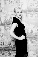 Blonde posing in black dress on background wall black and white