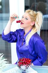 Blonde Frau isst Kirschen