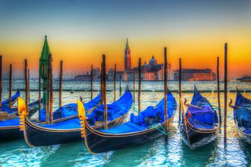 blue gondolas under a colorful sunset