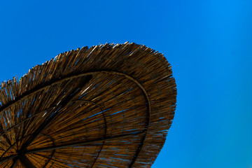 Пляжный бамбуковый зонт на фоне неба