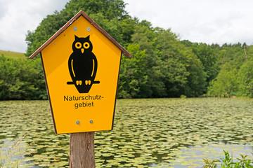 Schild Naturschutzgebiet mit See und Bäumen