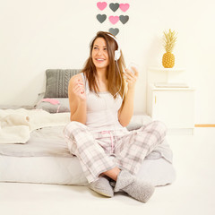 Teenage girl with headphones and smartphone in bed in morning