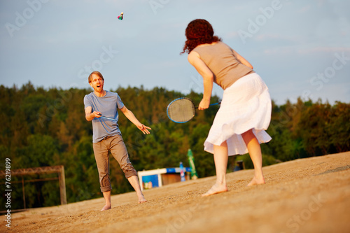 canvas print picture Paar spielt Federball am Strand im Sommer