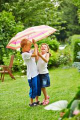 Zwei Kinder unter Regenschirm bei Regen