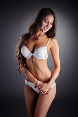 Smiling busty woman posing in white underwear
