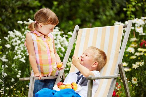 canvas print picture Zwei Kinder essen Obst aus dem Garten
