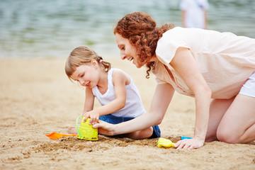 Familie spielt im Sand am Strand