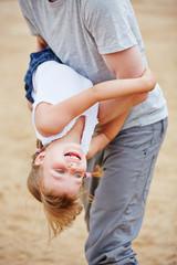 Vater tobt mit Tochter am Strand