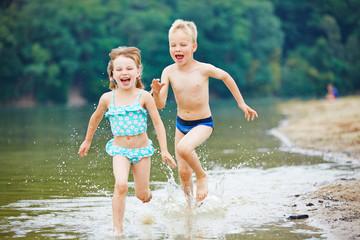 Zwei Kinder plantschen im Wasser