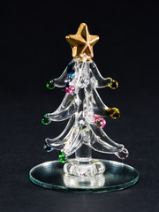 glass christmas tree over black background