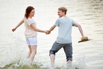 Paar läuft ins kalte Wasser im Sommer