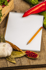 Spices and recipe book on wooden background.