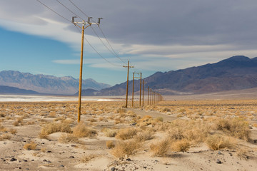 Power cable in desert valley with mountains in back side
