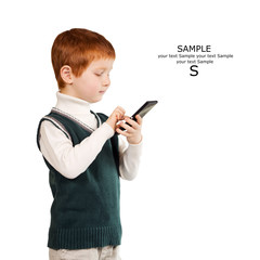 Cute red haired child stands looking at the smartphone. Isolated