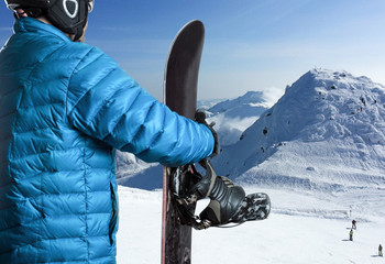 Sportsman with snowboard standing in the mountains