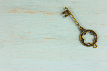 Antique brass key on a pale green distressed wood background.