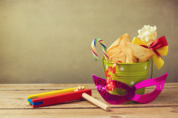 Hamantaschen cookies with grogger noise maker and carnival mask