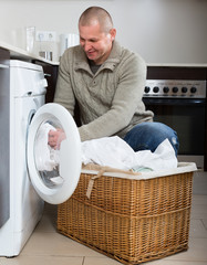 Smiling guy using washing machine