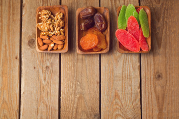 Assorted dry fruits and nuts on wooden table. View from above