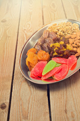 Assorted dry fruits and nuts on plate over wooden background