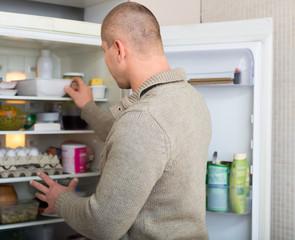 Man searching food in freezer