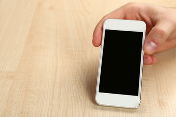 Hand holding smart mobile phone on wooden table background