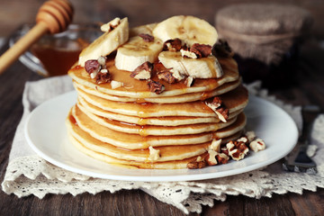 Stack of delicious pancakes with chocolate, honey, nuts and