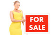 Blond woman holding for sale sign