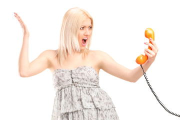 Angry woman holding a telephone speaker