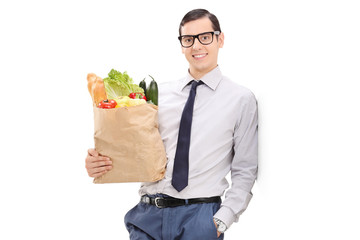 Elegant man holding a grocery bag and leaning against a wall