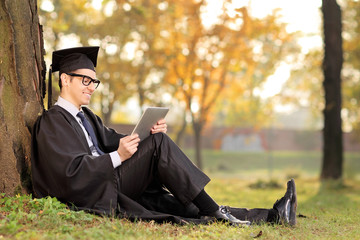 College graduate working on a tablet seated in park