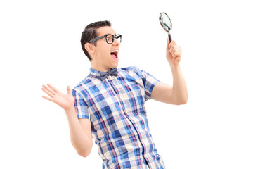 Excited man looking through magnifier