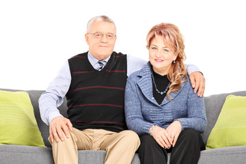 Lovely mature couple posing seated on sofa