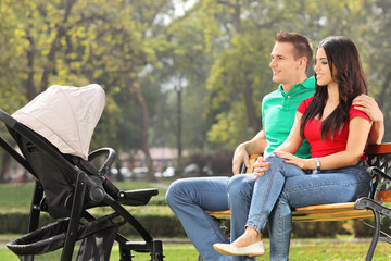 Young parents sitting with their baby in park