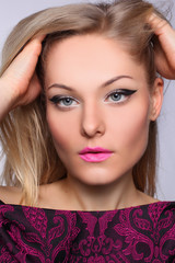 portrait of a beautiful blonde woman with make-up arrow