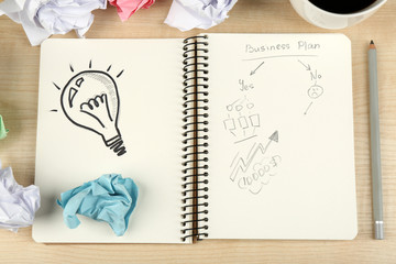Symbol of idea as light bulb in notebook with crumpled paper