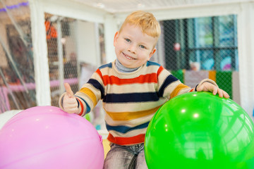 Little boy surrounded by colourful balloons
