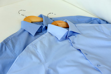 Blue shirts on hanger, on white armchair background