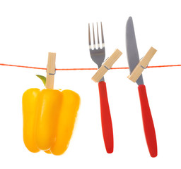 Fork, knife and bell pepper hanging from clothesline isolated