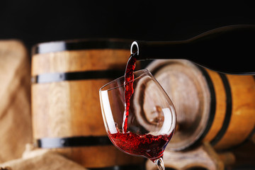 Pouring red wine from bottle into glass with wooden wine casks