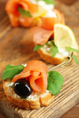 Canapes with salmon, black olive and herbs