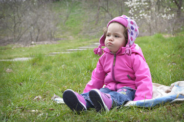 Little offended girl sitting on the spring meadow.