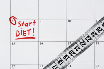 Diet concept - measure tape on calendar, close up