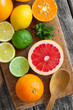 Halves of fresh citrus fruits on wooden background. Orange, grap