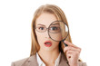 Businesswoman looking into a magnifying glass