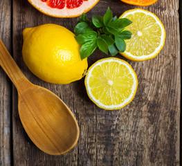 Halves of citrus fruits on wooden background. Orange, grapefruit