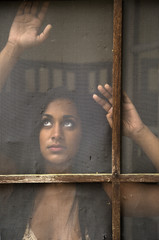 Young Indian Woman Gazing out Old Screen DOor